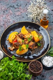 Крупным планом вид вкусного ужина с мясным картофелем, подаваемым с зеленью в черной тарелке и бутылке чесночного масла со специями