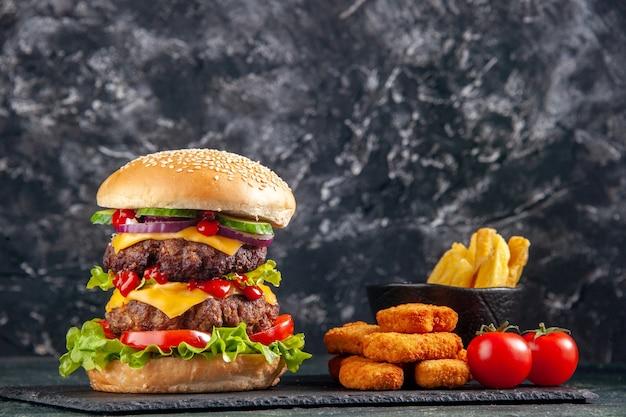 어두운 색 트레이에 맛있는 고기 샌드위치와 검은 색 표면에 치킨 너겟의 뷰를 닫습니다
