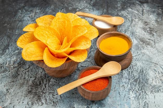 灰色のテーブルの上にスプーンで花の形をしたさまざまなスパイスのように飾られたおいしいポテトチップスのクローズアップビュー