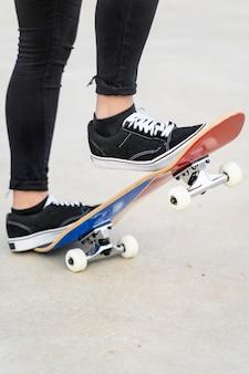 ハーフパイプでライドを開始する準備ができているスケートボードで10代の足のビューを閉じます。
