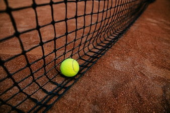 Close-up view of tennis ball caught in the net. On the court.