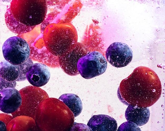 ネオンの光の中で明るいベリーと角氷で冷たくて新鮮なレモネードのクローズアップビュー。ガラスのマクロ泡で夏の飲み物を冷やすテクスチャ。表面の上部に浮き上がったり浮いたりします。