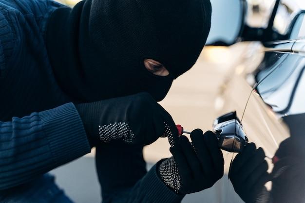 검은 옷을 입고 머리에 발라클라바를 얹은 위험한 남자의 가까이서 보면 훔치는 동안 곡괭이로 자물쇠를 따는다. 자동차 도둑, 자동차 절도 개념