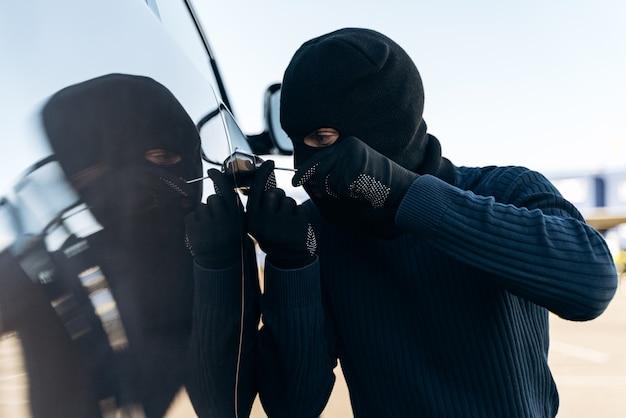 검은 옷을 입은 위험한 남자가 머리에 발라클라바를 하고 도둑질하기 전에 쇠지레로 차 한 잔을 깨려고 준비하는 모습을 가까이서 볼 수 있습니다. 자동차 도둑, 자동차 절도 개념
