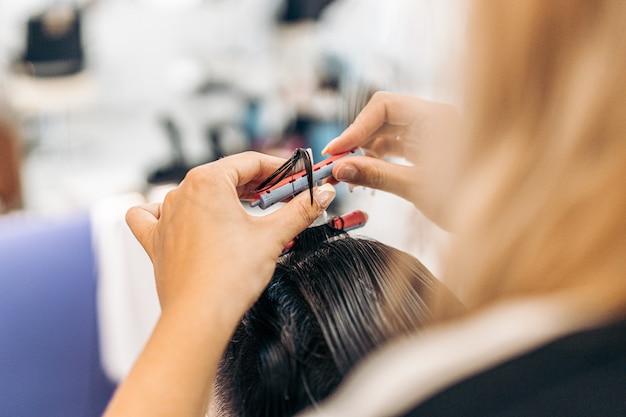 롤러를 사용하여 고객의 머리를 말리는 여성 미용사의 손을 클로즈업