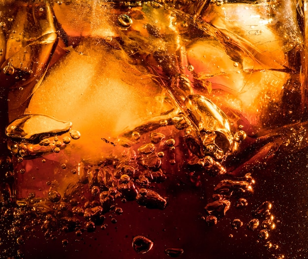 어두운 콜라 배경에서 얼음 조각보기를 닫습니다. 유리 벽에 거품과 매크로 거품과 달콤한 여름 음료를 냉각의 질감. 표면 위로 떠오르거나 떠 오릅니다.