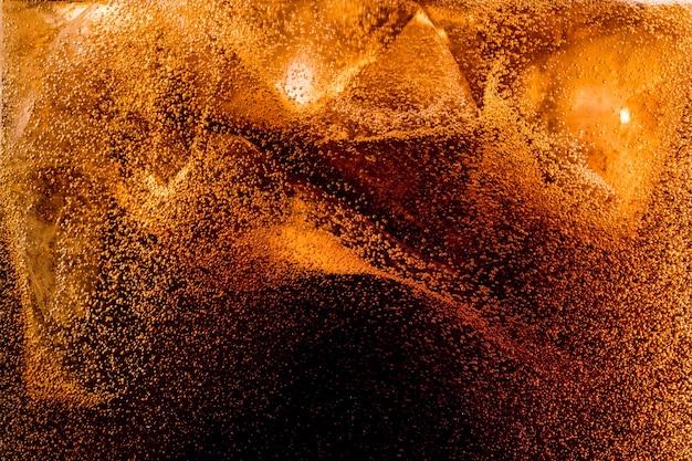 暗いコーラの背景に角氷のクローズアップビュー
