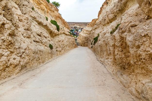 바위 형성의 근접 보기입니다. 매끄럽게 연마된 돌담 사이의 사막 트레일.