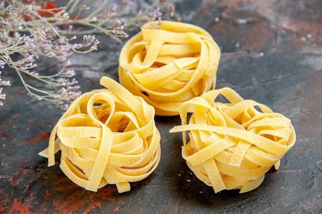 混合色のテーブル上の未調理のスパゲッティの3つの部分の拡大図
