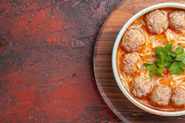 暗い背景の茶色のボウルに麺とトマトミートボールスープのクローズアップビュー