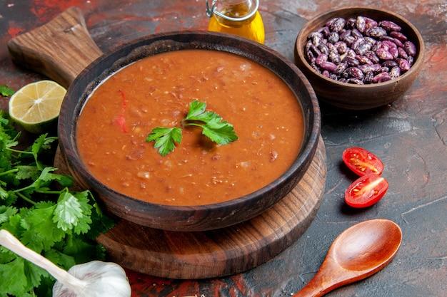 혼합 색상 테이블에 커팅 보드에 토마토 수프와 콩의 뷰를 닫습니다