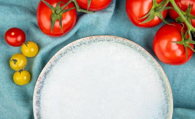 青い布の背景にトマトと空のプレートのクローズアップビュー