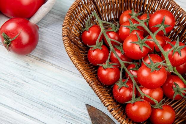 나무 테이블에 바구니와 다른 것들에 토마토의 근접 촬영보기