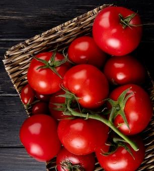 Взгляд конца-вверх томатов в плите корзины на деревянном столе