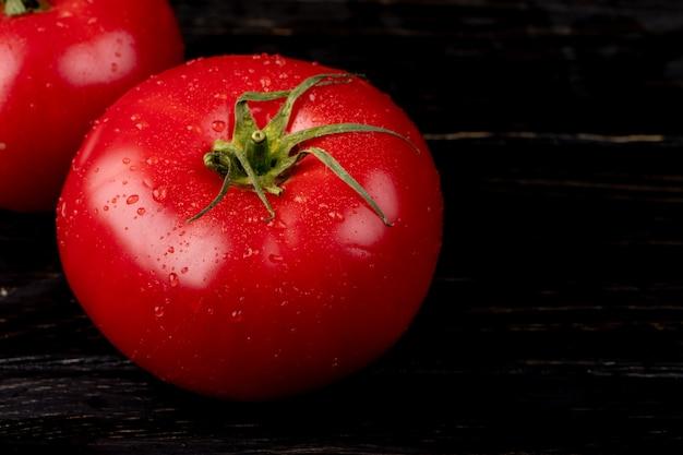 Взгляд конца-вверх томатов на деревянном столе с космосом экземпляра