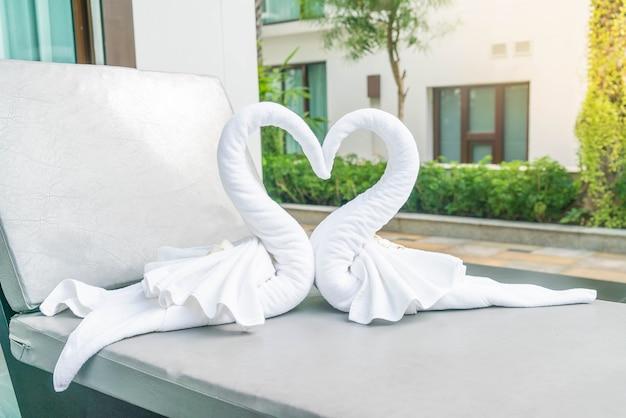 침대에 두 개의 좋은 수건 백조의 뷰를 닫습니다