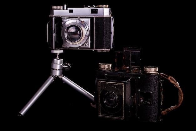 검은 배경에 고립 된 두 복고풍 빈티지 사진 카메라의 뷰를 닫습니다.