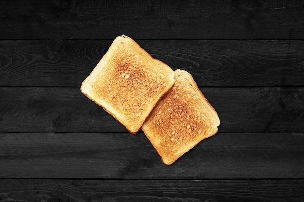 Закройте вверх по взгляду жареного хлеба двух ломтиков изолированного на черном деревянном столе.