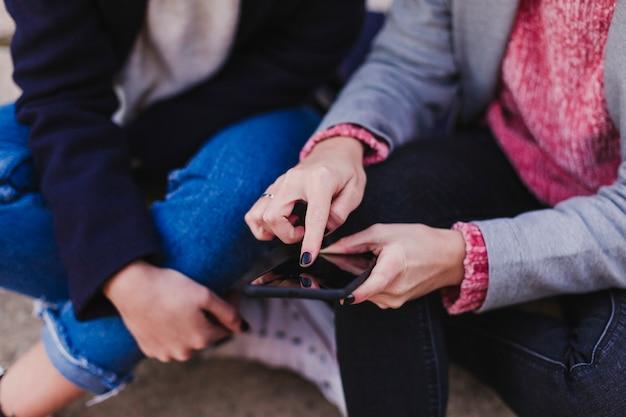 Крупным планом вид двух неузнаваемых женщин, сидя на полу и с помощью мобильного телефона