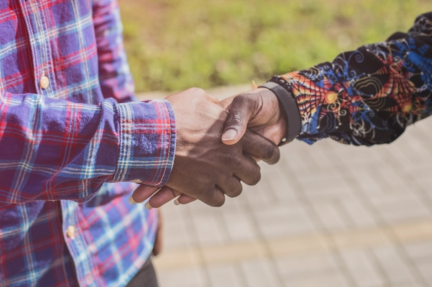 天気の良い日に都市公園の外で握手する暗い肌のトーンを持つ2人の若いアフリカ人男性のクローズアップビュー