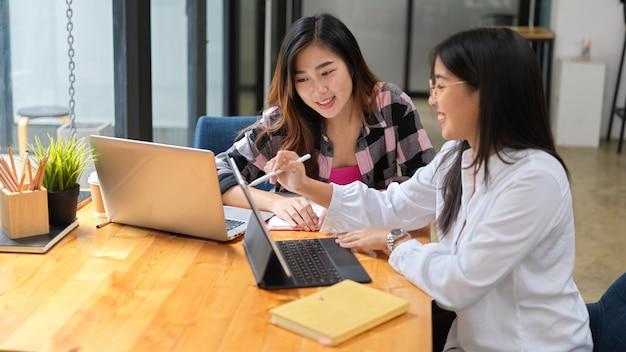 Крупным планом вид двух молодых студенток, вместе выполняющих групповое задание в библиотеке