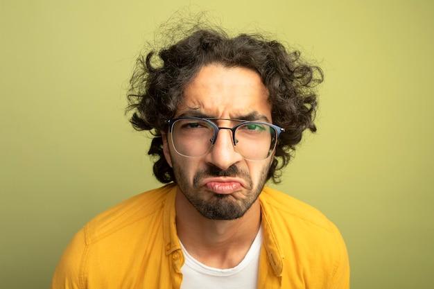 Крупным планом вид недовольного молодого красивого кавказца в очках, смотрящего в камеру, изолированную на оливково-зеленом фоне