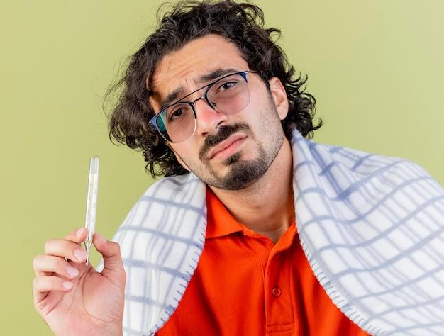 올리브 녹색 벽에 고립 된 전면을보고 격자 무늬 지주 온도계에 싸여 안경을 쓰고 불쾌한 젊은 아픈 남자의 근접 촬영보기