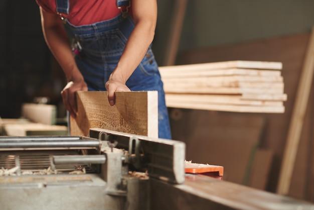 Крупный план неузнаваемого плотника в джинсовой одежде, обрабатывающего деревянную доску на деревообрабатывающем станке