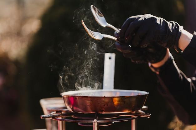 Крупным планом вид до неузнаваемости шеф-повара, приготовление пищи на открытом воздухе кухни.