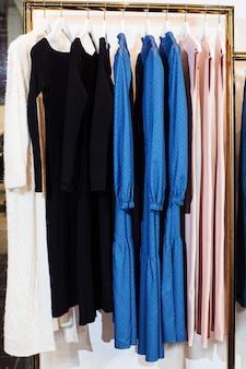 Крупным планом вид различной стильной одежды, висящей на вешалках в бутике