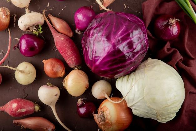 적갈색 배경에 보라색과 흰색 양배추 무 양파로 야채의 근접 촬영보기