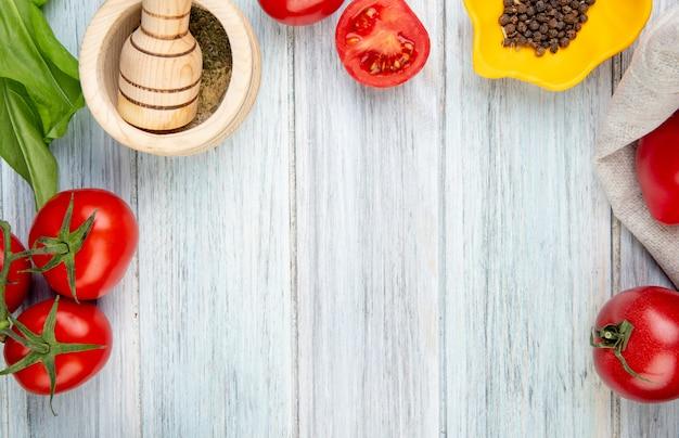 복사 공간 나무 테이블에 검은 후추 마늘 크러셔와 토마토 시금치로 야채의 근접 촬영보기