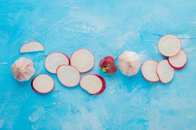 복사 공간와 파란색 배경에 전체와 얇게 썬 무와 마늘 야채의 근접 촬영보기