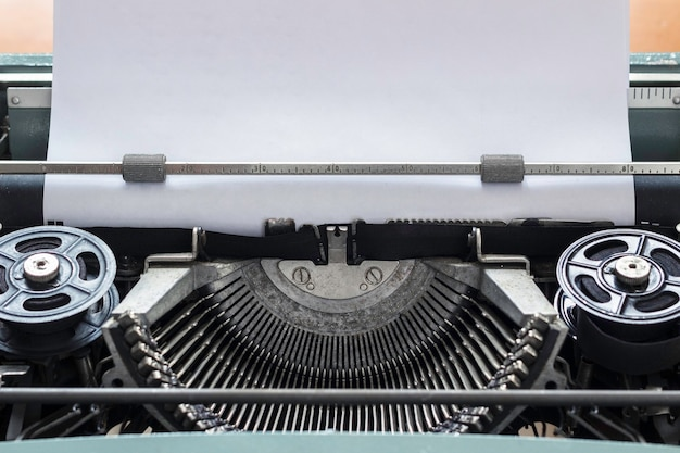 白紙の紙に新しい物語を書く準備ができているヴィンテージタイプライターバーのクローズアップビュー。スペースをコピーします。