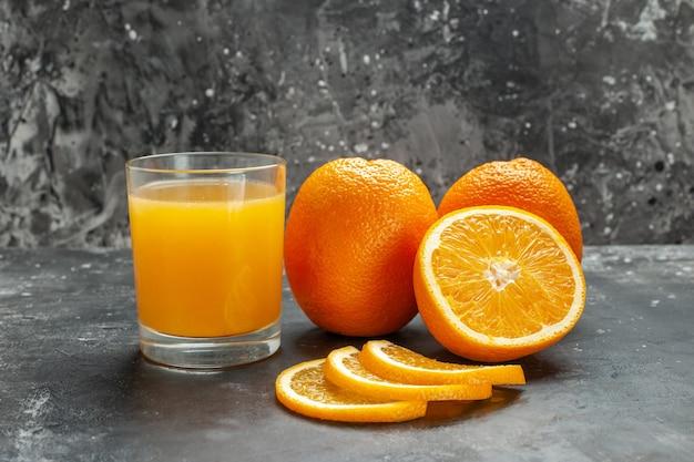 회색 배경에 잘게 잘린 신선한 오렌지와 전체 신선한 오렌지를 자른 비타민 소스의 클로즈업 보기