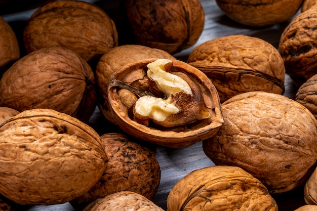 Крупным планом вид грецких орехов закрытых и разбросанных разбросаны по деревянному