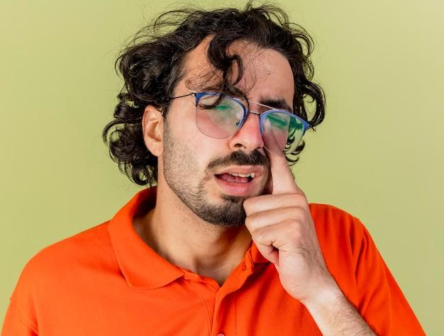 올리브 녹색 벽에 고립 된 안경을 쓰고 닫힌 눈으로 코를 만지고 약한 젊은 아픈 남자의 근접 촬영보기