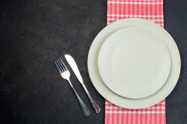 여유 공간이 있는 검정색 배경의 왼쪽에 빨간색 벗겨진 수건과 스테인리스 칼 붙이 세트에 흰색 빈 접시의 보기를 닫습니다