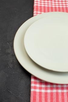 여유 공간이 있는 검정색 배경의 왼쪽에 있는 빨간색 벗겨진 수건에 있는 흰색 빈 접시의 보기를 닫습니다.