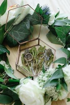 Крупным планом вид белых цветов, обручальных колец в деревенской коробке с растениями внутри