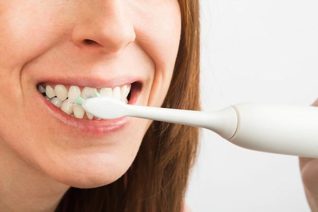 Крупным планом вид белых здоровых зубов женщины с электрической зубной щеткой