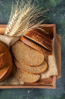 Крупным планом вид целого и нарезанного свежего черного хлеба на полотенце в коричневой деревянной коробке, гончарные специи на поверхности темных цветов