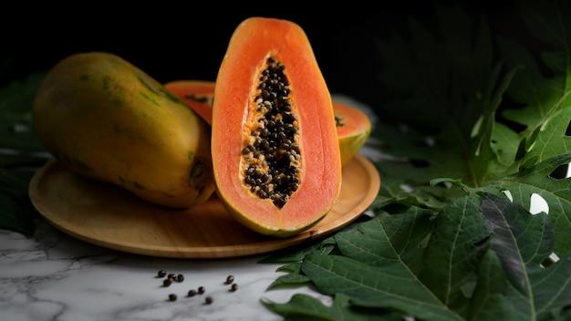 Крупным планом вид всей и наполовину сладкой папайи на деревянной тарелке