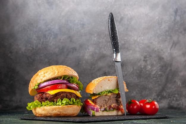 어두운 혼합 색상 표면에 검은 쟁반에 줄기 칼로 전체 잘라 다양한 맛있는 샌드위치와 토마토의 뷰를 닫습니다