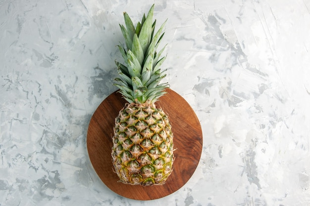大理石の表面のまな板に新鮮な黄金のパイナップル全体のクローズアップビュー