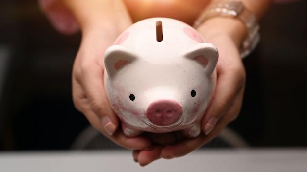 여자 손 잡고 돼지 저금통의보기를 닫습니다. 돈을 절약하고 개인 저축을위한 투자 또는 전략을 만드십시오.