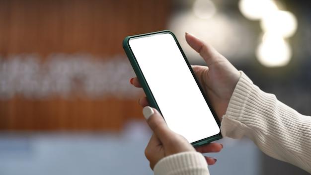 Крупным планом вид руки женщины, держащей макет смарт-телефона с офисным размытым фоном.