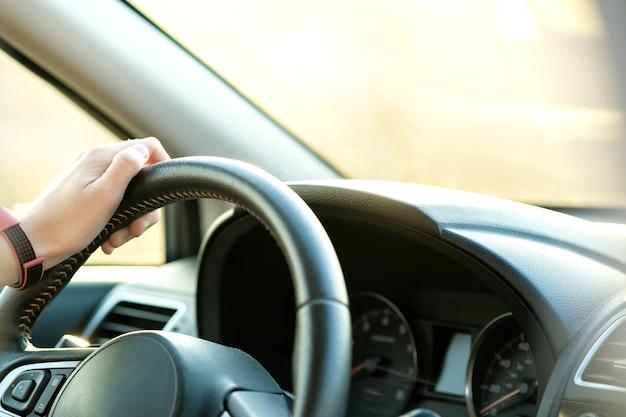 화창한 날에 도시 거리에서 차를 운전하는 스티어링 휠을 들고 여자 손의 뷰를 닫습니다
