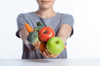 Close-up view of woman holding fresh ripe apple and vegetables