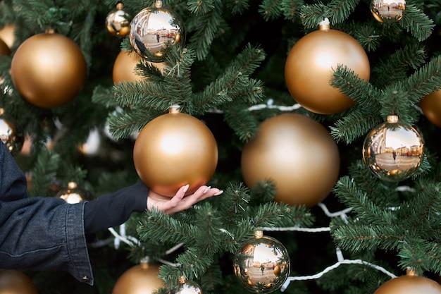 크리스마스 트리에 황금 공을 들고 여자의 손보기를 닫습니다.